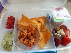 Nachos with spiced shredded chicken, fresh salsa and guacamole, mixed nuts, strawberries and yogurt.