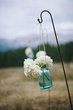 White bouquets in blue mason jars for Telluride, Colorado wedding with photos by Chowen Photography | via junebugweddings.com