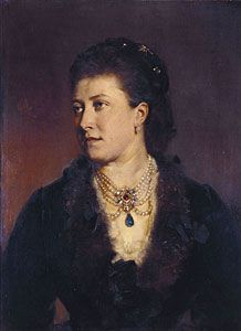Princess Helena (Princess Christian of Schleswig-Holstein) wearing a very large pendant composed of seven large handsome diamonds, with a ruby in the centre, and a large emerald drop; the stones were taken out of Indian jewels presented to Her Majesty in 1863. The pendant was given to the princess by the queen as a wedding present. In her hair are four diamond hair-pins. These had belonged to the Duchess of Kent (Queen Victoria's mother) and were also given to the princess by the Queen.