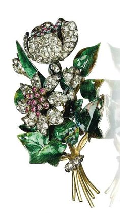 AN ANTIQUE ENAMEL, DIAMOND AND RUBY BROOCH Designed as a spray, the flowerheads and buds set with old-cut diamonds and cabochon rubies, to the translucent green and golden brown enamel leaves, mounted in silver and gold, circa 1850