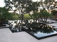 This project combines the Lautner knife-edge perimeter overflow with a vanishing edge on one side. The spa is an elevated perimeter overflow, which allows two levels of reflection on the black interior pool and spa. The raised planters help frame the view and add more focused reflection on the surface. Pool Builder: The Batts Company, Jacksonville, Florida