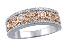 A novel, alternating pattern of two leaves and a single larger circles bedecked with rare, natural pink diamonds is flanked by two crisp lines of radiant white diamonds, in this rather unique fashion ring.