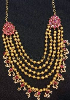 Antique gold ruby necklace is a grand and contemporary neckpiece to wear for weddings. Five strings of antique gold balls necklace with gorgeous ruby clasps on both sides Coral Jewelry, India Jewelry, Temple Jewellery, Beaded Jewelry, Indian Jewellery Design, Latest Jewellery, Jewelry Design, Indian Wedding Jewelry, Bridal Jewelry