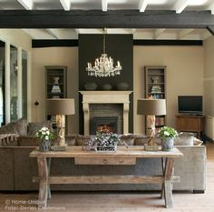 I like the table behind the sofa idea and background contrasting colored wall with fireplace.