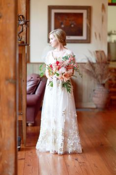 bride in lace wedding dress with large pink, white and red bouquet at spring / summer outdoor wedding