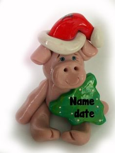 Christmas ornament polymer clay pig in pink 2 inches with green tree and red santa hat. $7.00, via Etsy.