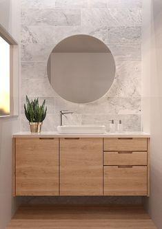Scandinavische badkamer inspiratie met grijze natuursteen achtige tegels. Daarnaast een heel mooi houten meubel met diverse lades. De ronde spiegel maakt het helemaal af. Ook zo'n prachtige badkamer? Klik dan op de foto!