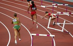Bulgaria's Vania Stambolova (R) crashes into a hurdle as Lithuania's Egle Staisiunaite (L) and T'Erea Brown of the U.S. run in the women's 400m hurdles round 1 heat during the London 2012 Olympic Games at the Olympic Stadium August 5, 2012.