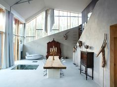 6 Amazing Homes Dug Into the Earth Photo 7 of 13 The house is surprisingly bright and welcoming inside, finished with a mix of exposed concrete and plain painted finishes. The rooms have either a cave-like atmosphere with daylight taken down through deep cuts in the hill, or large, open, southern-lit spaces in the front with views toward the surrounding woods.