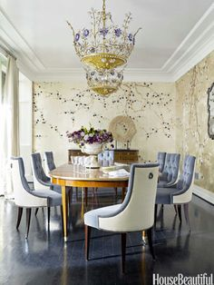 A 1940s French chandelier and de Gournay Plum Blossom wallpaper give the dining room a shimmery glamour. Thomas Pheasant dining chairs by Baker are covered in Kravet Versailles velvet and Lee Jofa Fiorentina Matelassé.