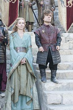 Un vestido muy elegante es de Cersei: colores azul y dorado, mangas amplias y largas, cinturón dorado, detalles en los hombros, el interior de las mangas es de un color dorado a juego...