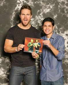 Stephen Amell with a picture of J2 posing with a picture of Arrow