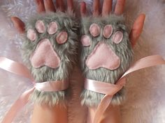 Pair of gloves made from fluffy grey faux fur fabric with fleece paw pads. (Pictured variation is pink paw pads with pink ribbons). These gloves are fingerless which make them possible to wear every day, as well as part of a costume, since you still have full use of your hands as well as adorably sweet paws. These gloves are designed as one size fits most - there is a ribbon stitched near the edge which can be tied to make them closer fitting at the wrist and of course these dangling ribbons…