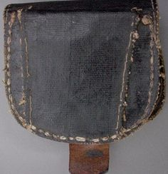 This unmarked percussion cap box is manufactured primarily of canvas, painted with a waterproof coating; generally referred to as tarred linen.  The body of the box is made of leather as are the end caps.  The front and back is made of a single piece of painted canvas with a wide painted canvas belt loop sewn on.  The closing finial is made of lead.  The closure tab is russet leather.