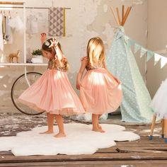Alfombra con forma de nube de Pilepoil, tipi mint con estrellas y guirnalda de banderines. Las niñas llevan vestidos de fiesta Pailletes de tul con lentejuelas. Todo de Bel and Soph.