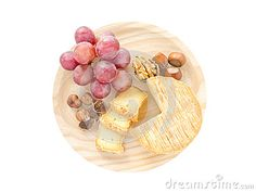 Soft washed-rind cheese, hazelnuts, walnut and red grape on the textured wooden board top view isolated on white