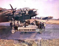 World War II, 1942, The crew of Lancaster bomber +Admiral Prune+ stands by as their plane is prepared for a mine-laying operation