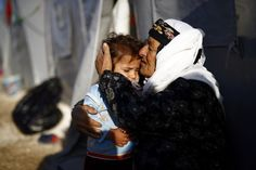 A Kurdish refugee woman from the Syrian town of Kobani hugs a child outside her tent in a camp in the southeastern town of Suruc, Sanliurfa province October 22, 2014.