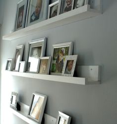 Create your own photo gallery using wall shelves... they have great ones at Ikea if you're close to one!