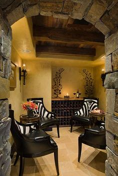 Wine room designed by Locati Interiors.  Animal print chairs.  Stone walls.Wood ceiling.Tile floor. Zebra print.  Rustic Mountain Lodge.
