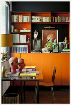 love the unusual colour of the rack and how it showcases not just books but art and figurines...the painted mask like heads on the desk,  echo the colour scheme of the rack, bringing it all together.