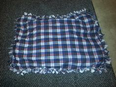 Diy dog bed! Two large pieces of fabric cut into strips around the edges and tied together,  stuffed with old t-shirts