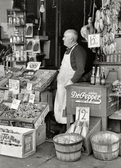 "November 1939. Waco, Texas. ""Proprietor of small store in market square."" Pop bottles on the cooler: Woosies, Double Line and Double Cola. 35mm nitrate negative by Russell Lee for the Farm Security Administration"