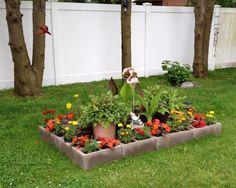 jardin en parpaings avec des fleurs au milieu de la pelouse