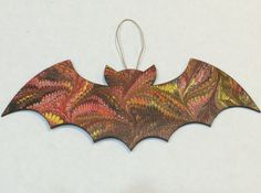 Cute bat decoration for Halloween! Add this little bat to your Halloween collection all on its own, or spice up one of your current decorations like a wreath or a tree!  Hand marbled wooden bat with hemp loop for hanging. Bat measures approximately 9 w x 4 h  ************************************************************************************  Marbling by floating paints on the surface of a liquid is thought to have been developed in the 15th century in central Asia. Paint is speckled onto a…