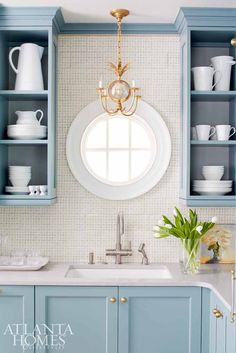 Blue cabinetry in scullery with round window over sink and white dishes in open shelving