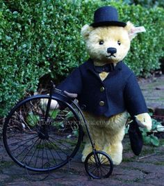 Steiff teddy bear with 'penny-farthing' velocipede,  - 2006,   This yellow-blond real gentleman Steiff bear is made in a  limited edition of 1250 pieces and comes with his own miniature version  of black bicycle with Steiff logo from the late 1800's. He wears black felt  tails with a black top hat and a black bowtie. He carries a little black bag  with 'Karstadt' embroidery in blue. He has flat feet that allow him to stand  on his own. Felt paws, his nose and claws are handstitiched in…