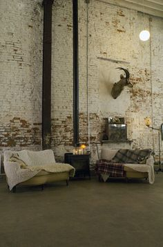 exposed brick // vintage sofas // mismatched throw rugs