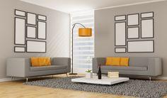 Minimalist living room with 2 grey sofas, orange pillows, orange lamp, grey rug and white coffee table platform