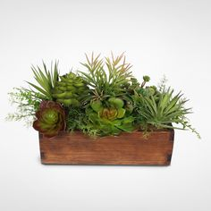 A robust artificial succulent arrangement featuring Echeveria and Sedum Succulents in an attractive Wood Planter. Sprengeri Grass and Leather Ferns accent the piece, adding texture and buoyancy. Perfect for indoor or outdoor settings and suitable for a variety of decor.Wood Planter11