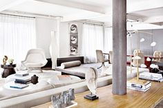 Gray Modern Loft Living Room; New York-based interior designer Julie Hillman converted a former warehouse into an elegant, eclectic home with sculptural furniture and contemporary photography; photo by Manolo Yllera; Domain Home; This is an example of contemporary design that mixes different styles/elements, including some Mid-Century Modern pieces (like the white chair on the left) and global/international accessories.