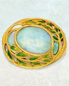 Louis Comfort Tiffany for Tiffany & Co. - An Arts and Crafts Gold, Opal and Enamel Brooch, Circa 1905. Centring an oval-shaped cabochon opal within openwork foliate surrounds, flanked by two smaller cabochon opals, decorated with leaves applied with translucent green enamel, signed Tiffany & Co.