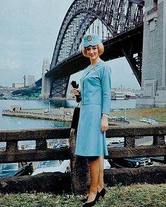 Flight stewardess next to Sydney Harbor Bridge wearing Qantas airline uniform worn from 1964 to