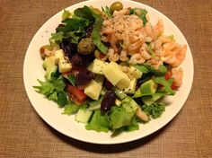 Salaattia, rucolaa, baby pinaattia, lehtikaalia, avokadoa, kurkkua, tomaattia, paprikaa, juustoa, katkarapuja, oliiveja, sitruunaoliiviöljyä ja mustapippuria.