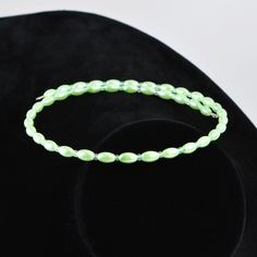 You'll look simply elegant in this simple iridescent green glass choker. Or make it a bright gift for a sunny soul. This lightweight memory wire choker features mint green oblong beads punctuated by translucent green seed beads. A bright, cheery look for the warm days ahead. Memory wire is easy to wear and care for. It expands to fit all without losing its shape.  The Smallest Planet Guarantee  All Smallest Planet jewelry is handmade by me, Sara Kelly, in my home studio in San Diego, Cali...