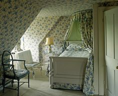 Blue Floral bedroom; the same pattern is used in this entire space for continuity. Too many different pattern could break up the space and make it seem smaller. Bold choice to match bedding, curtains, AND wallpaper. It works in this attic bedroom.