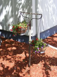 Found old metal rake @ flea market for $6. Two small stainless steel colanders picked up @ area Salvation Army for $2 ea...added replacement hanging basket chains ($1.50 per pk.) Finished product= hanging basket décor.  Used old burlap feed sack as liners!