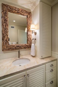 The focal point of this neutral guest bathroom is a driftwood framed mirror, adding interest and texture to the space. The ivory colored vanity features a tan quartzite countertop. Driftwood Mirror, Bathroom Styling, Guest Bathroom, Bathroom Mirror, Glamorous Bathroom Decor, Bathroom Wall Cabinets, Guest Bathrooms, Bathroom Design, Bathroom Decor