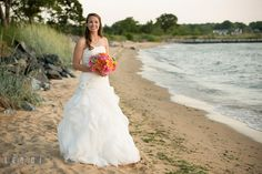 HER DRESS!  Bride posing on the beach holding gorgeous floral bouquet by florist Intrigue Design and Decor. Kent Island Maryland Chesapeake Bay Beach Club wedding photo, by wedding photographers of Leo Dj Photography. http://leodjphoto.com