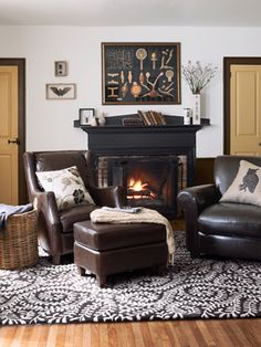 a pair of leather club chairs and an ottoman, all by Bradington-Young, sit atop a Dash & Albert rug; the print over the fireplace reproduces a century-old lithograph of spores.