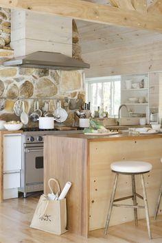 cocinas modernas pequeñas, cocina rústica con pared de piedra, madera clara, sartenes colgantes, campana extractora