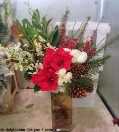 Perfect Christmas mix of amaryllis, ilex berries, pinecones, roses and orchids
