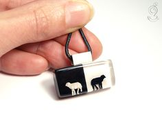 Black sheep – extraordinary sheep pendant with a black and a white mini-sheep in front of a black and white background made of resin   ///// © Isabell Kiefhaber www.geschmeideunterteck.de