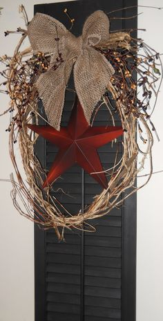 Primitive country large black wooden shutter with burlap bow, rusty star and honeysuckle vine