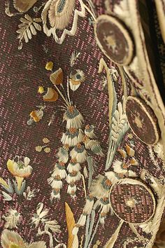 Detail embroidery, 3-piece court suit, Spain, 1775-1790. Brown silk velvet, lavishly embroidered with naturalistic flowers in polychrome silk; waistcoat: ivory silk satin, embroidered with polychrome silk in a complementary floral design.