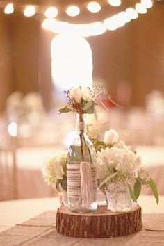 Rustic centerpiece made with bottles, yarn, and sliced log... it's just missing a lantern and candles!